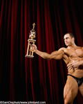 Picture of a bodybuilder proudly showing his trophy to the audience. The man is on stage wearing a black thong. The trophy is in the center of the picture.